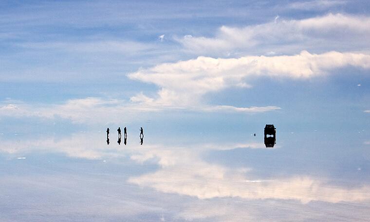 personas y vehículos sobre efecto espejo en Salar de Uyuni