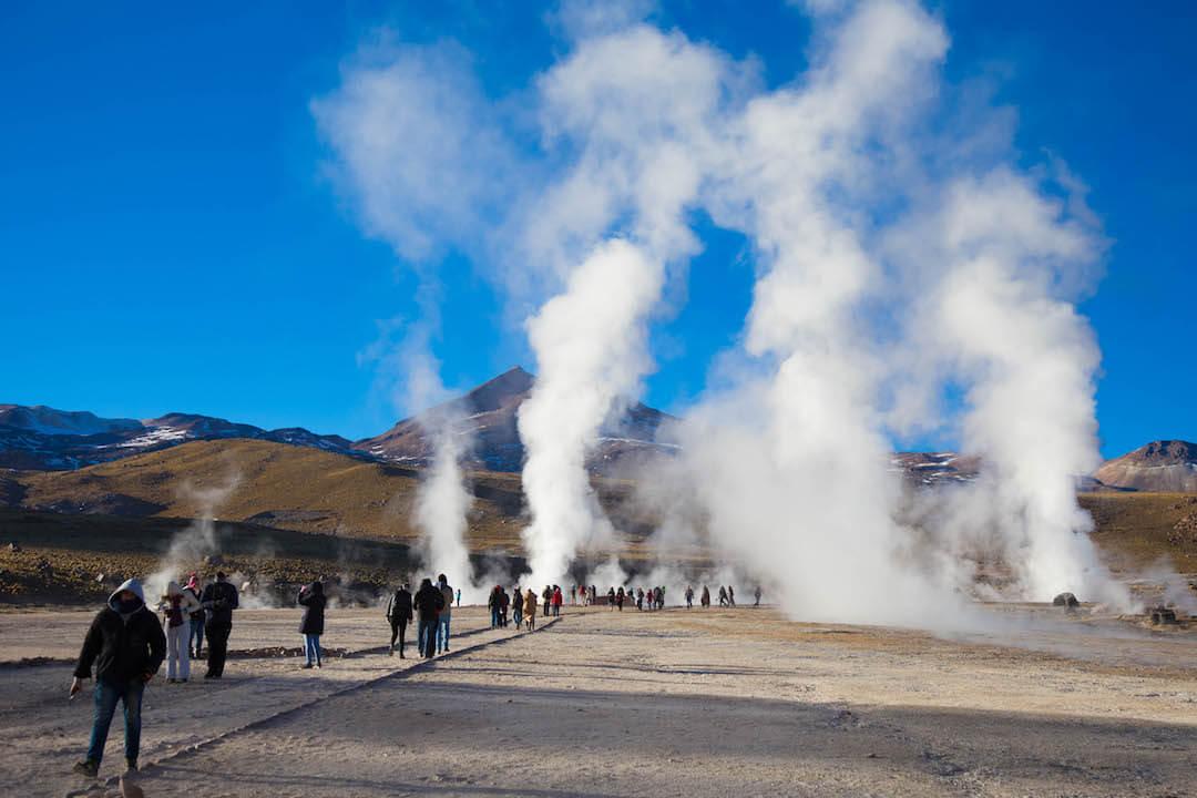 Turistas y geysers bajo un cielo despejado