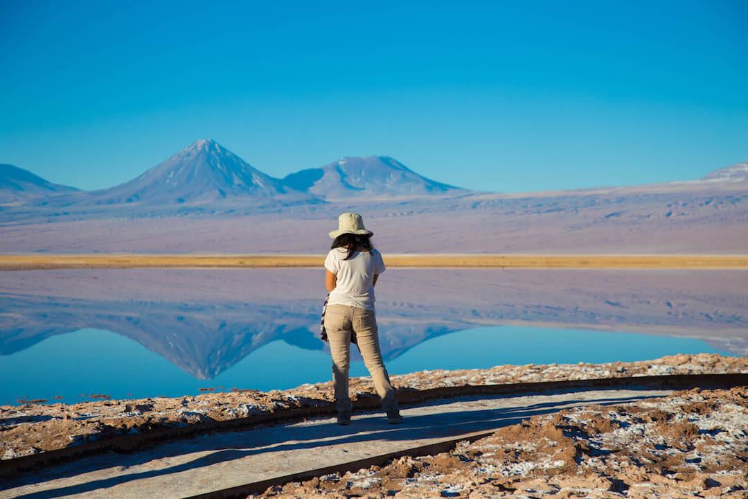 Turista frente a laguna y volcán.