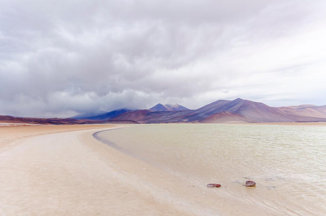 Laguna transparente y montañas bajo cielo nublado