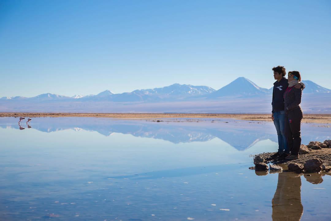 Pareja observa laguna y montañas en Salar de Atacama