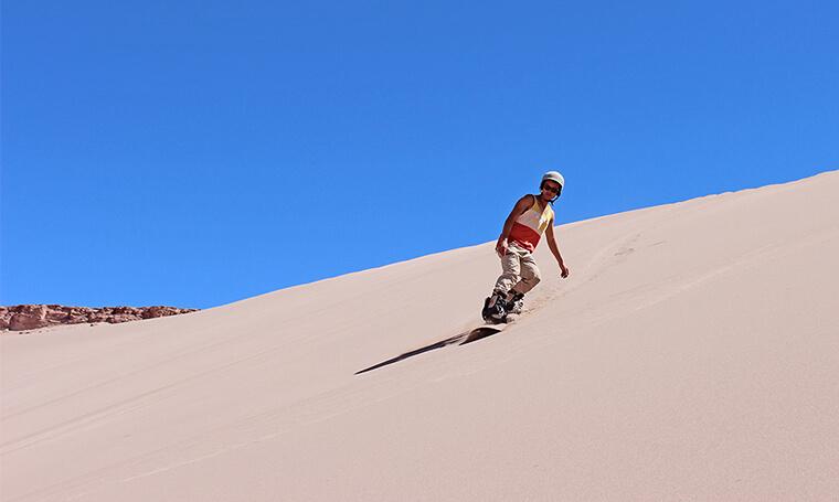 sandboarder desciende por una duna en el desierto