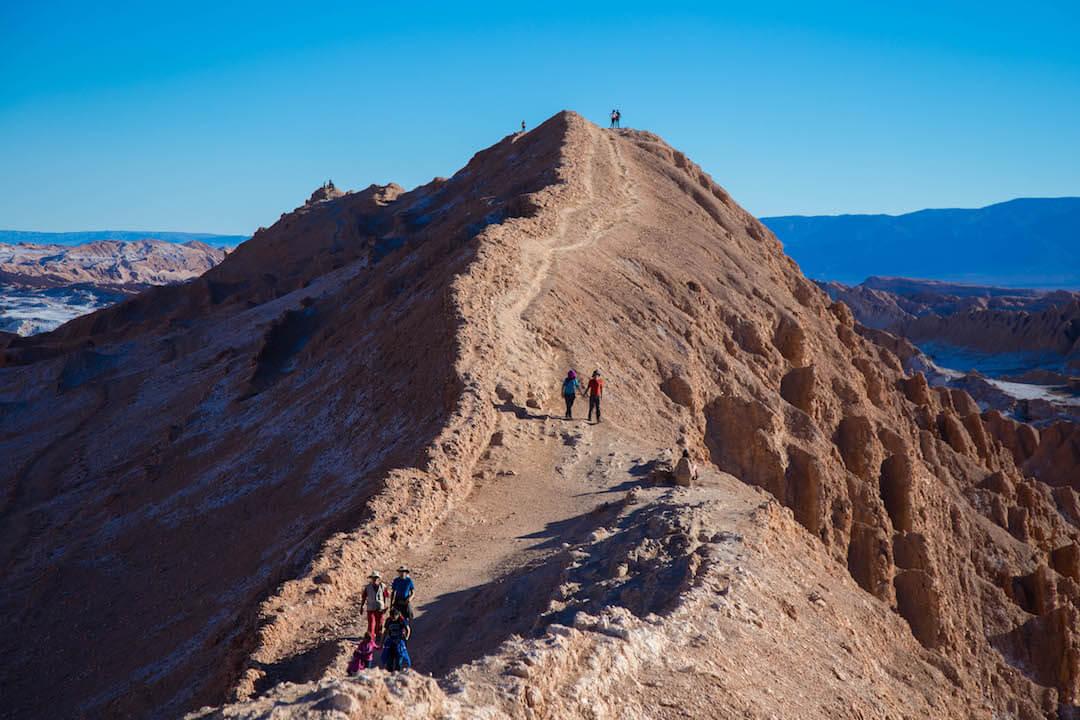 Personas caminan por un cerro de arena